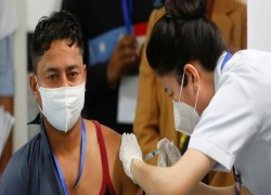 SANITATION WORKER GETS FIRST SHOT AS INDIA LAUNCHES VACCINATION CAMPAIGN